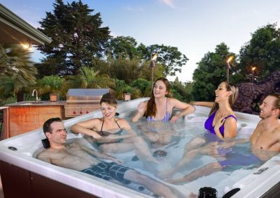 A mixed group of men and ladies enjoy an Arctic Spa hot tub
