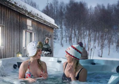 Girl Friends in the snow enjoying an Arctic Spas hot tub at night